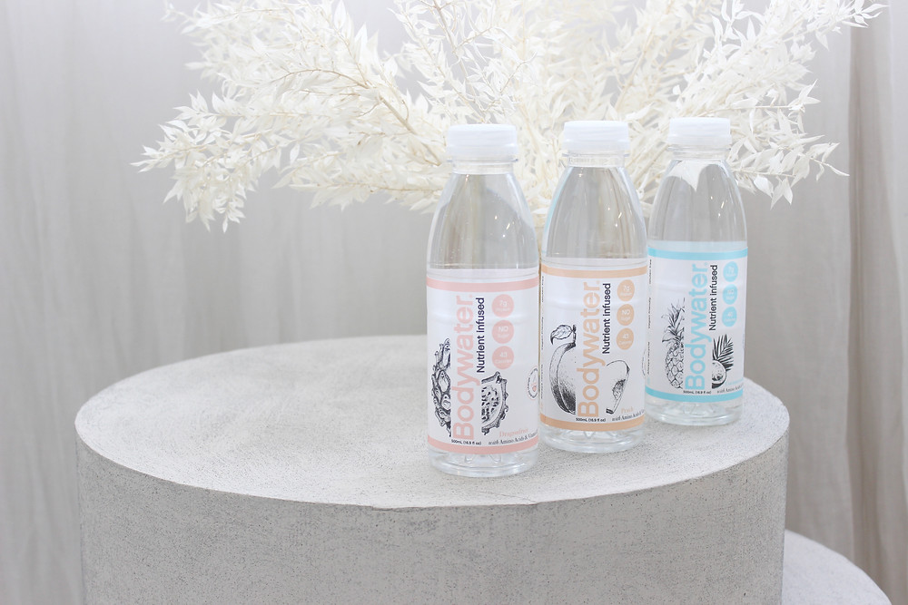 Three bottles of Bodywater on a side table in front of white flowers.