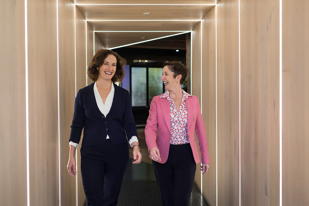 Two women in suits walk down a hallway.
