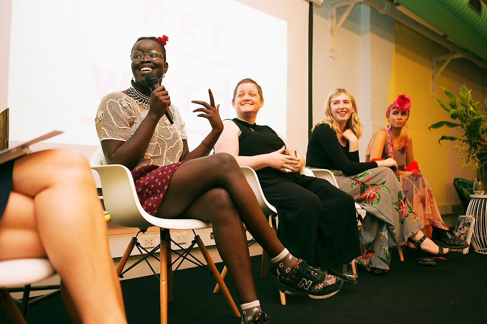 A group of women speak on a panel on stage.
