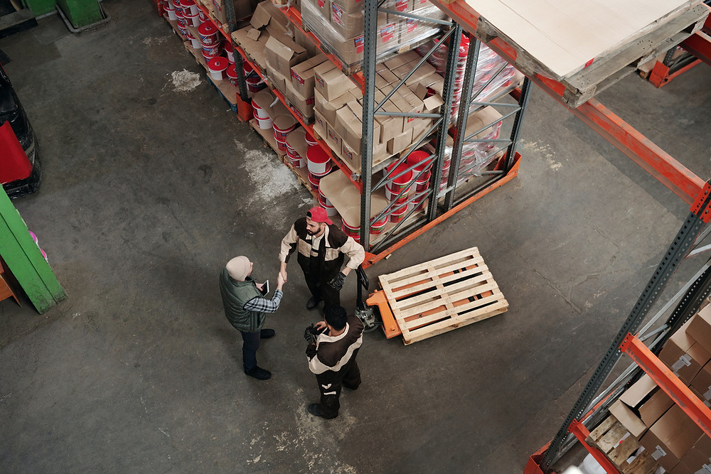 An aerial shot of warehouse workers shaking hands surrounded by stocked shelves.