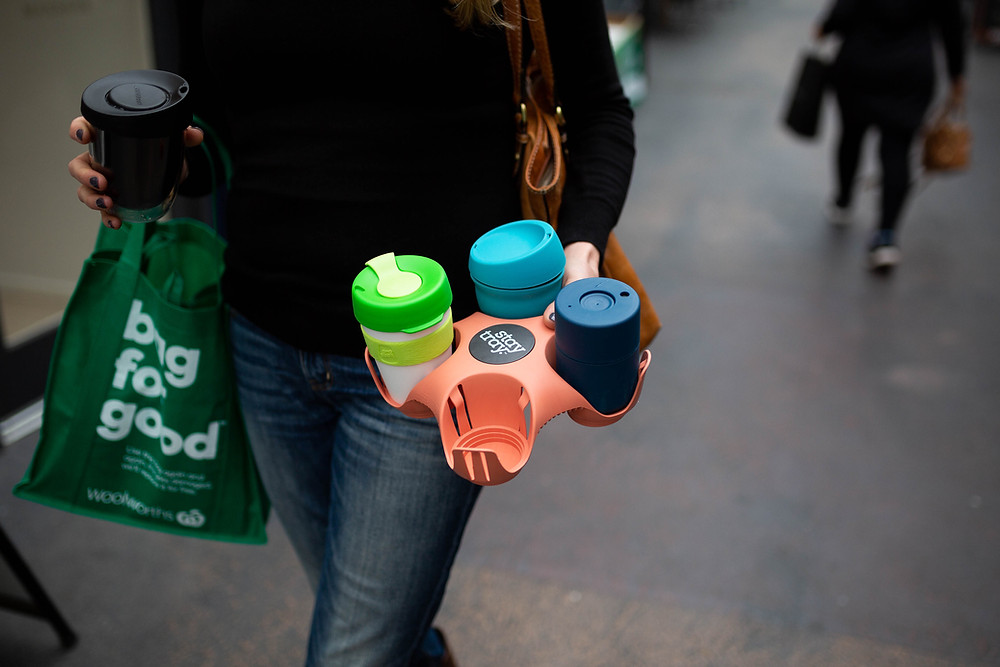 A person walks holding a reusable tray with three reusable cups.