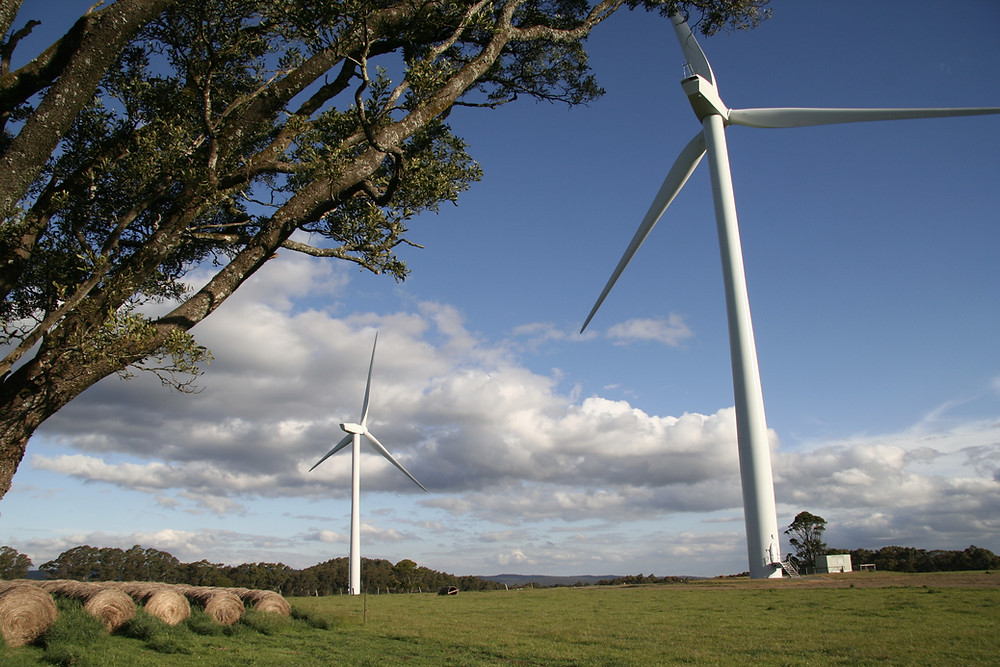 Two wind turbines on a grassy hill.