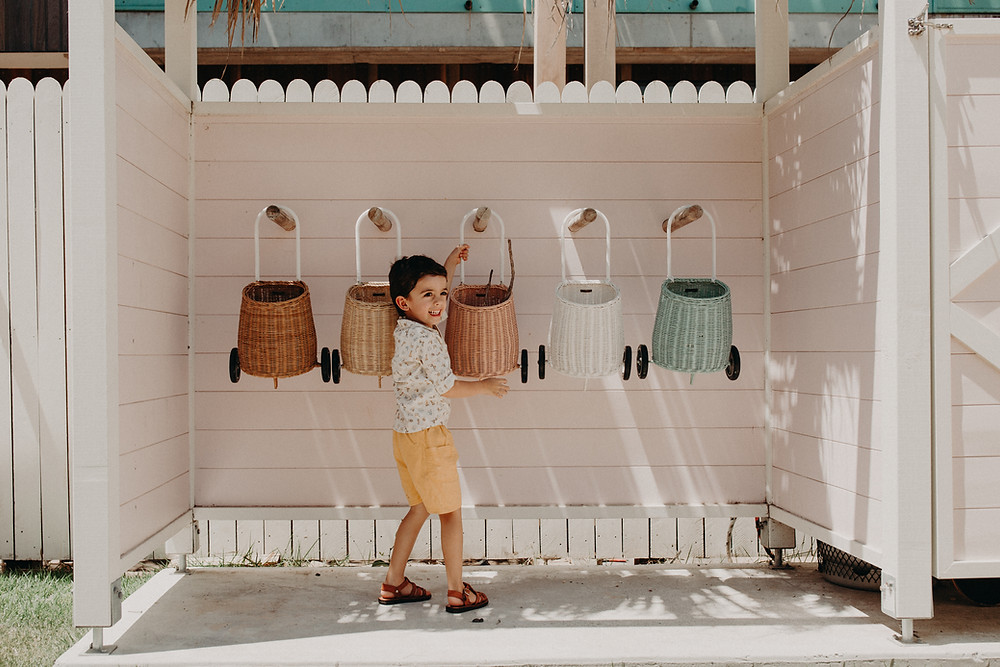 An excited young child reaches for a pink woven trolley with others hanging on either side.