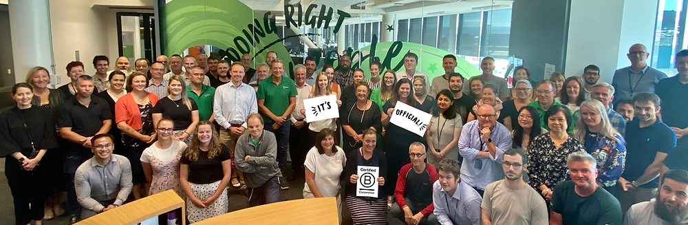 A group of The Co-operative Bank staff gather for a group photo with the B Corp logo.