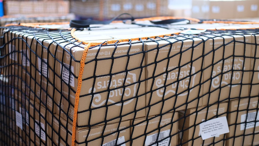 Chia Sisters boxes of juice are covered in a reusable net in the factory.