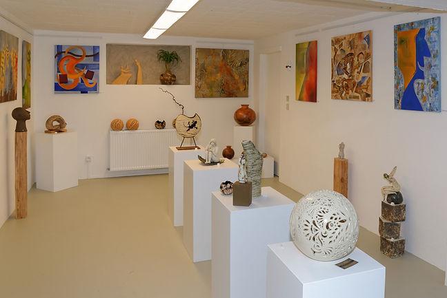 Vue partielle de l'Atelier Expo d'Art Le Tandem. Espace clair et accueillant, présentant diverses céramiques sur plots et tableaux peints fixés aux murs.