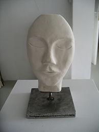 Pile ou face. Céramique sur support métallique.Tête chauve, yeux clos. Impression de calme, de douceur et de sérénité. Teinte blanche.