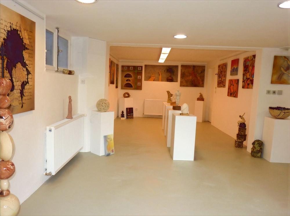 Hall d'exposition éclairé. Les murs sont garnis de tableaux d'art aux couleurs chaudes. Au centre, sculptures céramiques sur plots blancs