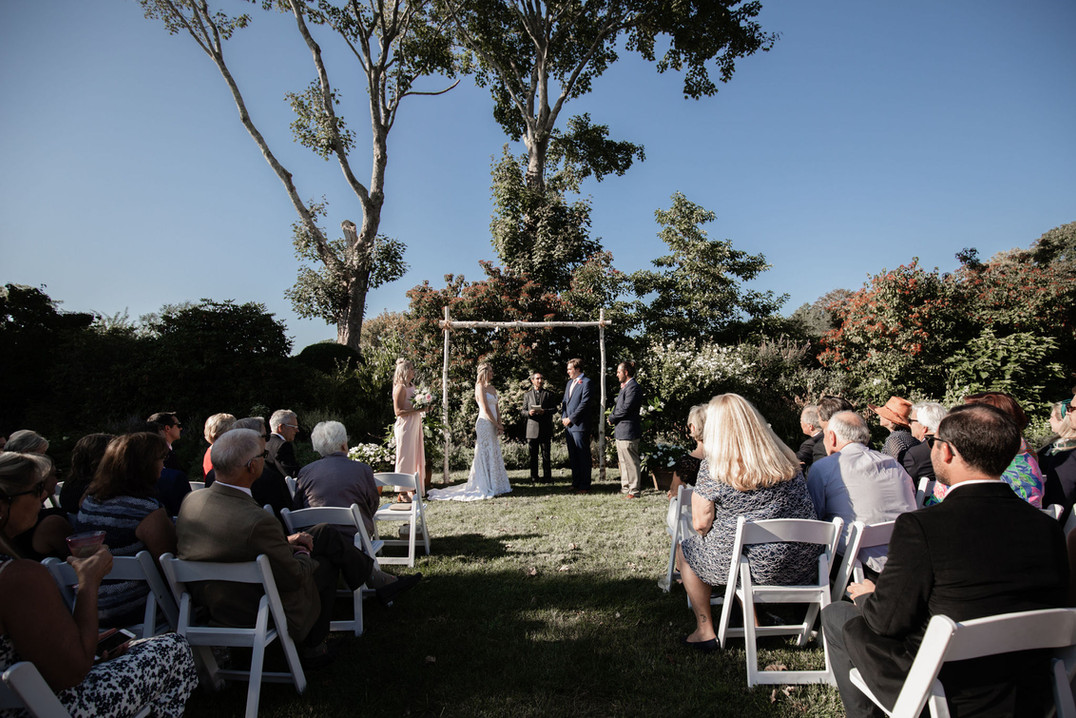 Ceremony by garden with crowd