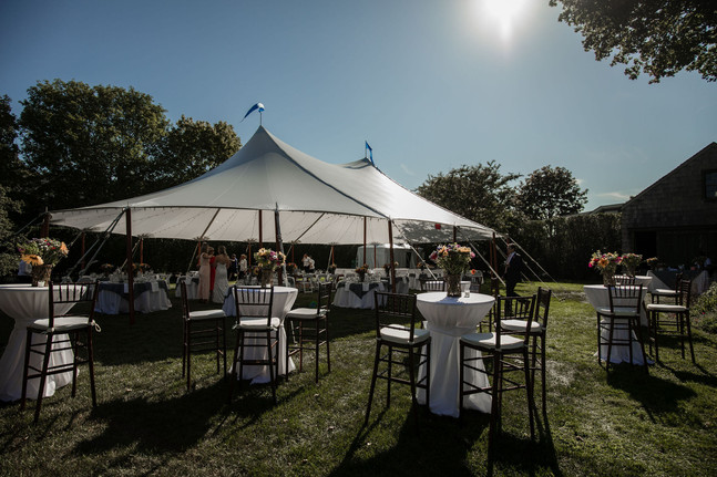 Tent in backyard with cocktail tables