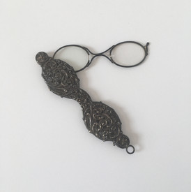 """This style of eyewear is called """"lorgnette,"""" deriving from the french """"lorgner,"""" meaning to take a sidelong look at. The first lorgnettes were developed in 1780 from scissor spectacles. Lorgnettes were popular in the 19th century, often used at the theater and opera. Women took interest in the lorgnette style, sparking new designs such as the """"jealousy lorgnette."""" The """"scissors"""" handle is intricate, showing the wealth of the owner. The lorgnettes are located in the hallway on the second floor."""