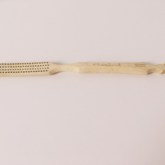 In the late 18th century, William Addis, an English entrepreneur, was thrown in prison after starting a riot. He soon became tired of cleaning his teeth with rags, soot, and salt. He collected bones from his meals, drilled holes, and laced pig bristles through the holes. When he was released from prison, he mass-produced his idea. This toothbrush on display was produced by the DuPont Corporation in 1935 and based off Addis's original design, inventing and introducing the use of nylon as an alternative to silk. The toothbrush on display has unfortunately lost its bristles over the years, but you can still see where the nylon was inserted into the holes. The toothbrush is located in Clara's Dressing Room on the second floor.