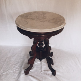 This white and grey oval marble top pedestal table is from the Madeleine White Estate. Although there are no inscriptions so pinpointing the year of production is hard, the use of marble for tabletops and the use of scrolls was implemented in furniture during the Rococo Revival (1845-1870). During this time, expensive woods were used for furniture, and when lesser woods were used, they were painted to appear of a higher grade. The more pricey woods were walnut, rosewood, and mahogany. Given that the inhabitants of Rogers Mansion were fairly wealthy, one could expect to find a piece of nice furniture such as this table in the house. The marble table is located in the Dining Room on the first floor.