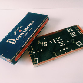 """The game of dominoes is believed to have originated in China, around 1120 CE, although there is debate on when they were brought over to Europe (most say the 14th century). The game later moved from France to Britain in the late 18th century (presumably from French POAs). The word """"domino"""" is believed to be of Latin descent from the word """"dominus,"""" meaning """"master of the house."""" But the word has evolved over the years, first being the French black and white hood worn by Christian priests during the winter, then to a masquerade hooded costume with a small mask, then to just the mask, and finally to the domino playing set (mainly the 1-1 tile). The dominoes are located in the hallway on the second floor."""
