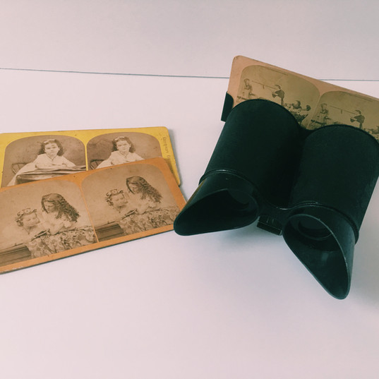This style of stereoscope is called a Holmes stereoscope, invented in 1861 by Oliver Wendell Holmes. Intended to be a more economical way to view pictures, the Holmes stereoscope consisted of only two lenses and a stand made of wood, to hold the stereocards. Due to its lightweight and portable design, this stereoscope remained in production for nearly a century, and sitting in the family room after the evening dinner and laughing over the stereo pictures became a normal occurrence in households. This stereoscope is from the Keystone View CO. in Meadville, P.A. The stereograph pictures are from a collection entitled Stereoscopic Treasures, photographed by F. G. Weller. The stereoscope is located in the hallway on the second floor.