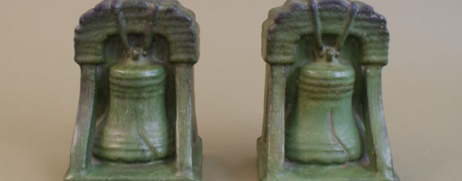 """A pair of Liberty Bell bookends glazed in mat green with curdling, accented with areas of dark shading. Both are impressed on bottom """"DENVER TERRA COTTA CO."""" A few chips to the backs and base edges.  Each measures 5"""" wide x 4"""" deep x 6.75"""" high. Please Call Us at (626) 437-6275 for More Information"""