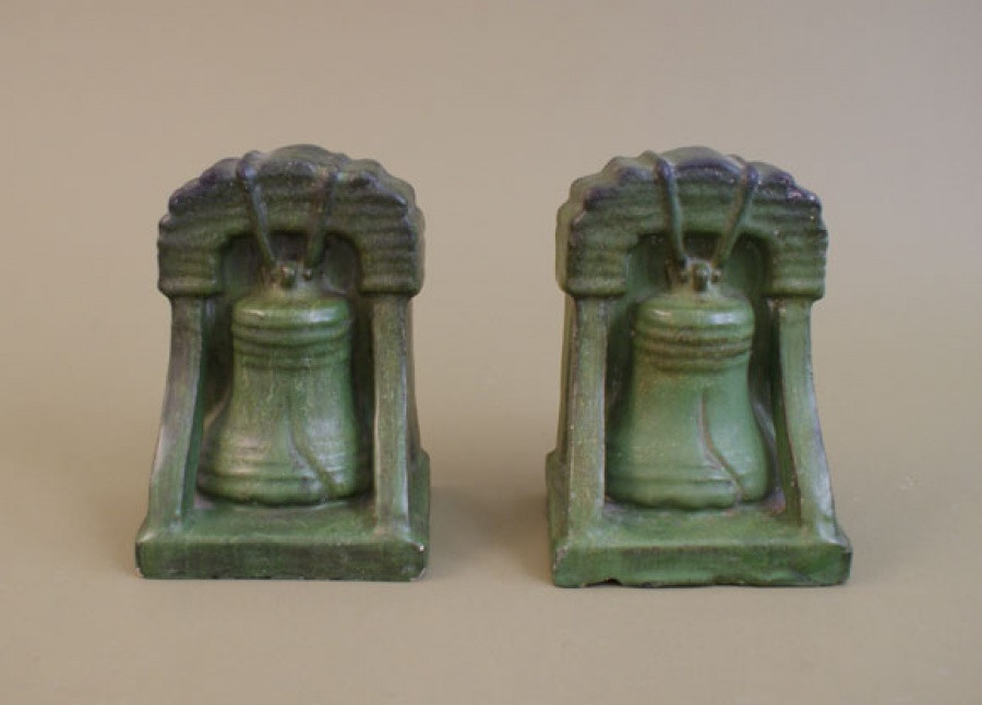 "A pair of Liberty Bell bookends glazed in mat green with curdling, accented with areas of dark shading. Both are impressed on bottom ""DENVER TERRA COTTA CO."" A few chips to the backs and base edges.  Each measures 5"" wide x 4"" deep x 6.75"" high. Please Call Us at (626) 437-6275 for More Information"