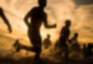 Silhouette of a group of swimmers runnin