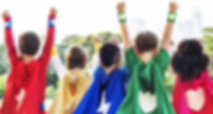 Superhero kids with their hands raised to the sky