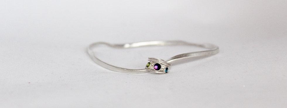 Ribbon bangle with gemstone set charm