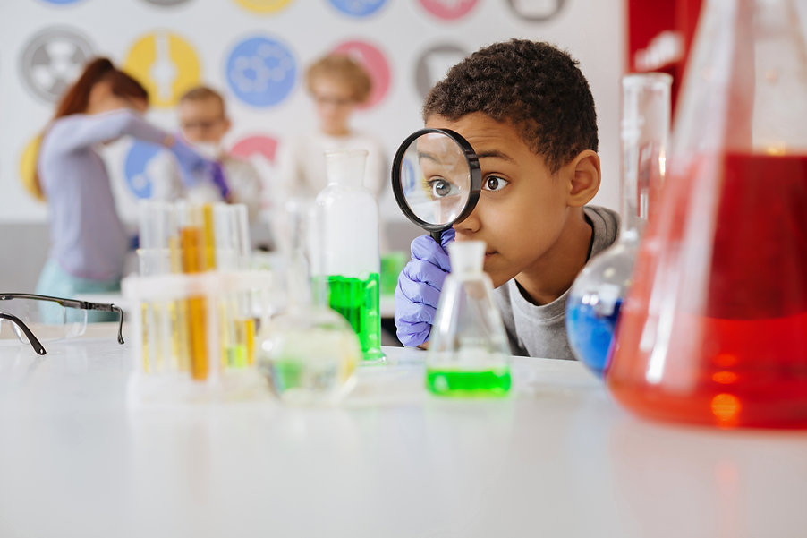 Helpful tool. Upbeat teenage boy looking at a chemical flask through a magnifying glass wh