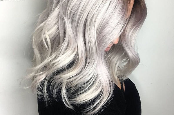 woman with long platinum hair color looking down, blonding hair round rock, platinum hair round rock