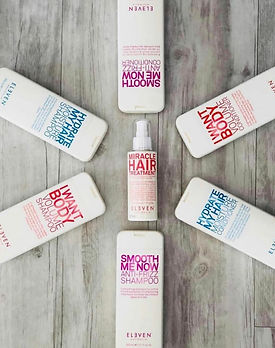 seven hair care products features on a wood floor