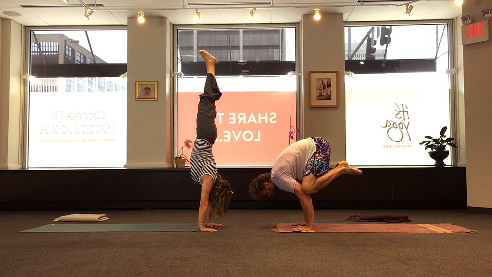 Marie Russel in handstand and her husband in crow