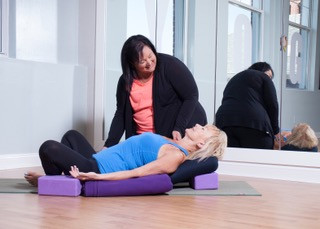 Yoga teacher Heather helping prop up a students in a restorative fish and bound angle pose