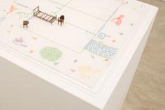 A planta [detalhe], 2017  Desenho bordado a mão sobre lenço de algodão branco, miniaturas de cama, cadeira e criado-mudo e caixa de acrílico Dimensões: 44 cm x 44 cm x 05 cm Fotografia: Junior Luis Paulo