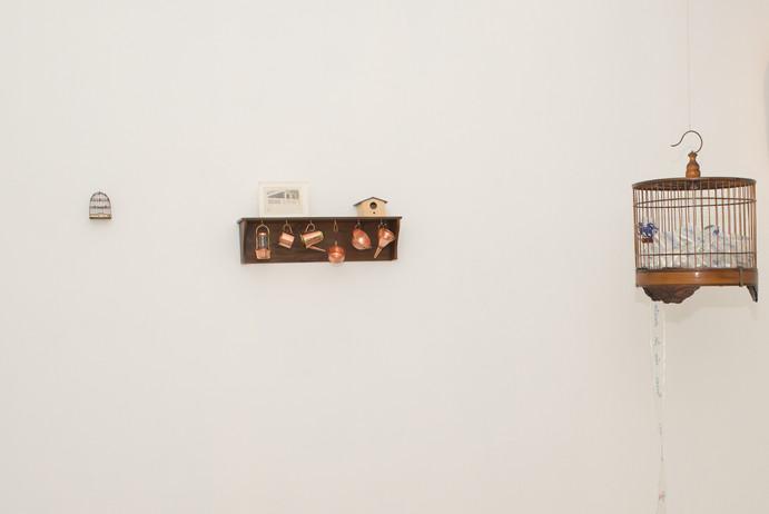 A cozinha [detalhes], 2017  Prateleira de madeira, miniaturas de cobre, casa de passarinho, fotografia original em caixa de acrílico, miniatura de gaiola, armário e jogos de chá Dimensões variáveis Fotografia: Junior Luis Paulo