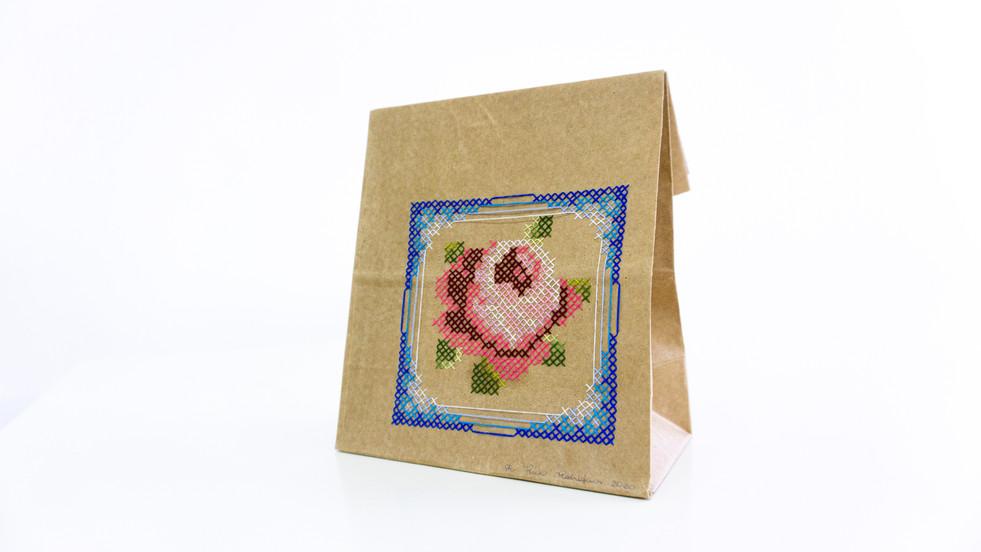 """Sem título, 2020  Série """"Rosa enquanto flor. Rosa enquanto cor. Roza enquanto avó"""" Bordado com ponto cruz sobre saco de papel de lanche (iFood) Dimensões: 21 cm x 18,5 cm x 10 cm"""