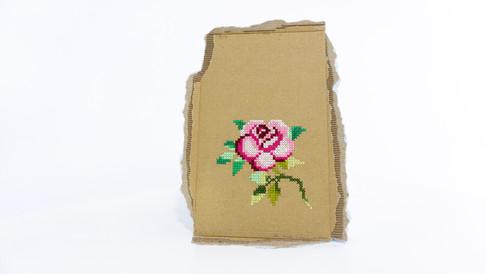 """Sem título, 2020  Série """"Rosa enquanto flor. Rosa enquanto cor. Roza enquanto avó"""" Bordado com ponto cruz sobre pedaço de papelão Dimensões: 38 cm x 27 cm"""