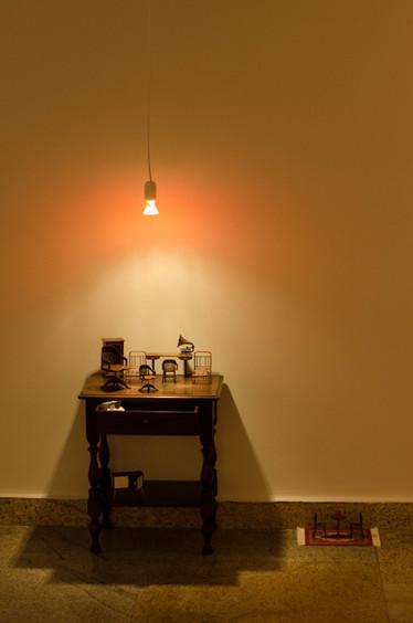 """Sem título [detalhe], 2016  Série """"Tudo o que não invento é falso"""" Mesa de madeira, miniaturas, lâmpada suspensa, desenhos e flor de brinquedo Instalação com dimensões variáveis  Fotografia: Junior Luis Paulo"""