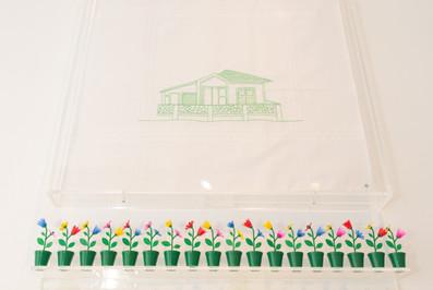 A casa, a chave, a fachada e o jardim [detalhe], 2017/18  Dobradura de papel branco 200g/m² e prateleira de acrílico; Chave de metal (objeto); Desenho bordado sobre lenço de algodão branco, brinquedos e prateleira de acrílico Dimensões variáveis Fotografia: Junior Luis Paulo