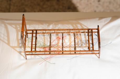 Sem título [detalhe],  2016  Fronha bordada, travesseiro, miniatura de cama e lâmpada suspensa  Instalação com dimensões variáveis Fotografia: Junior Luis Paulo