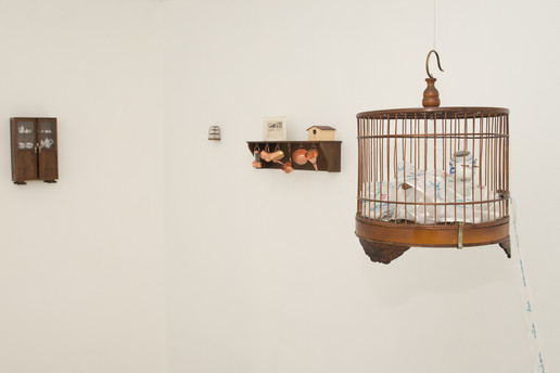 A cozinha, 2017  Prateleira de madeira, miniaturas de cobre, casa de passarinho, fotografia original em caixa de acrílico, miniatura de gaiola, armário e jogos de chá Dimensões variáveis Fotografia: Junior Luis Paulo