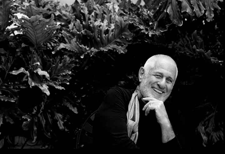 Portrait of Richard Saul Wurman in black and white. He is smiling with his hand on his chin.