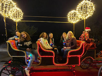 A group of people on an Large Illuminated Christmas Carriage.