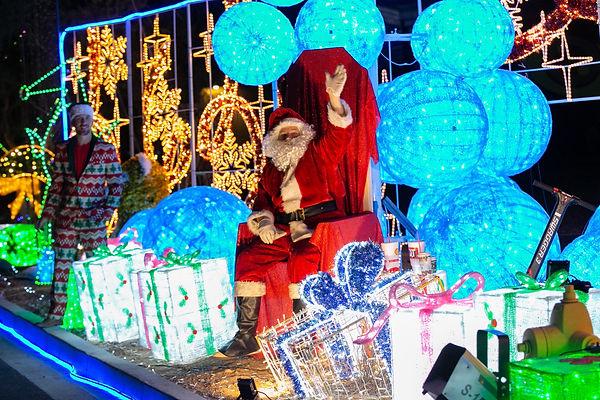 Santa and his helper waving while he sits around Christmas Lights