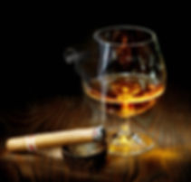 lit cigar from central cigars lying next to a glass of scotch at sabor latino 2018