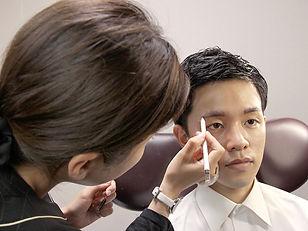 男性の眉をデザインしている女性