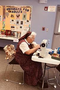 Woman sewing at sewing machine.