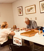 Man and woman sitting at a table making a repair.