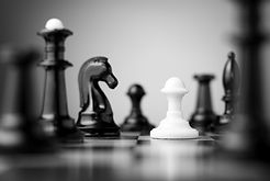 white pawn surrounded by black chess pie