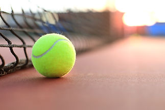 Bright greenish yellow tennis ball on cl