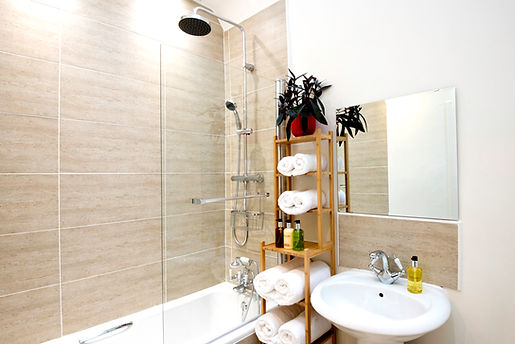 Luxurious bathroom with rain shower, deep white bath and fluffy towels at The Five Turrets