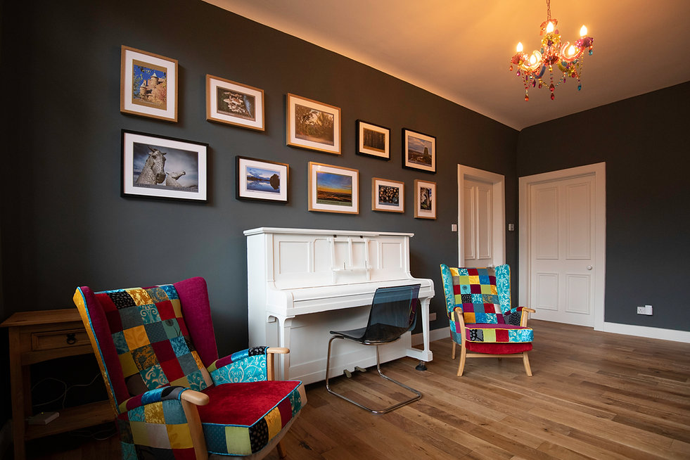 A white piano, a gallery of pictures, patchwork chairs, solid wood floor and a chandelier provide a colourful welcome to The Five Turrets, the stylish holiday home in the Scottish Borders