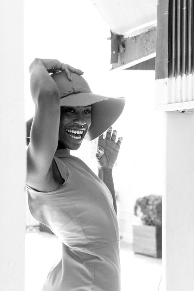 black woman with hat laughing by fleur l