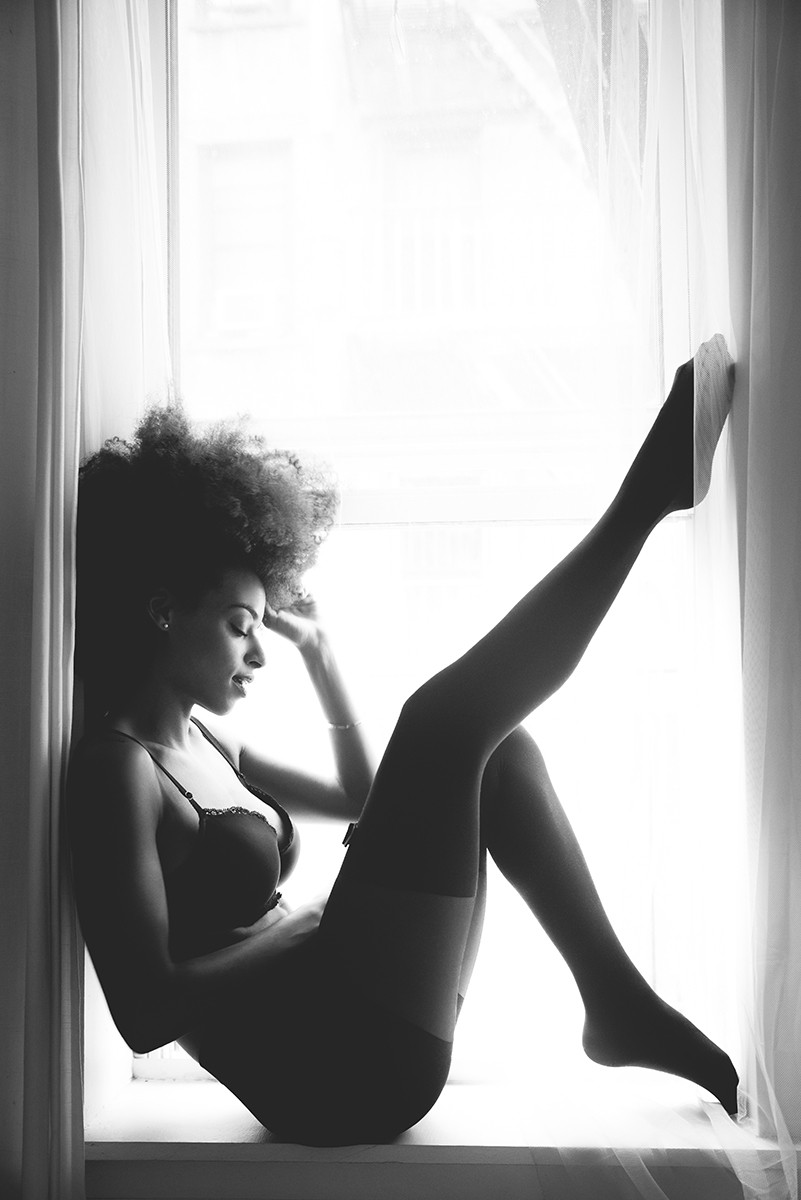black woman sitting in the window natural light by fleur losfeld